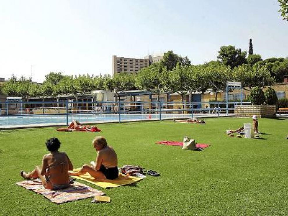 Varias usuarias de una piscina municipal tomando el sol.