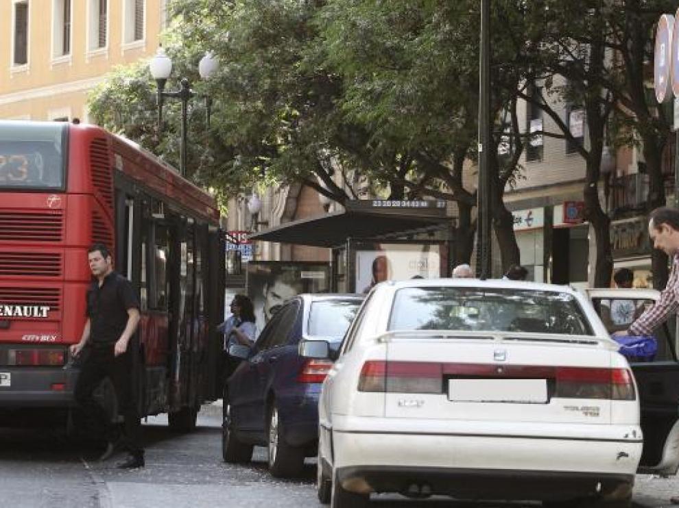 Dos turismos, aparcados ayer en una parada de autobús de la avenida de César Augusto.