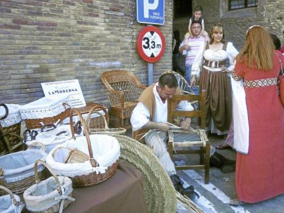 Un artesano elabora una cesta en uno de los puestos del mercado medieval.