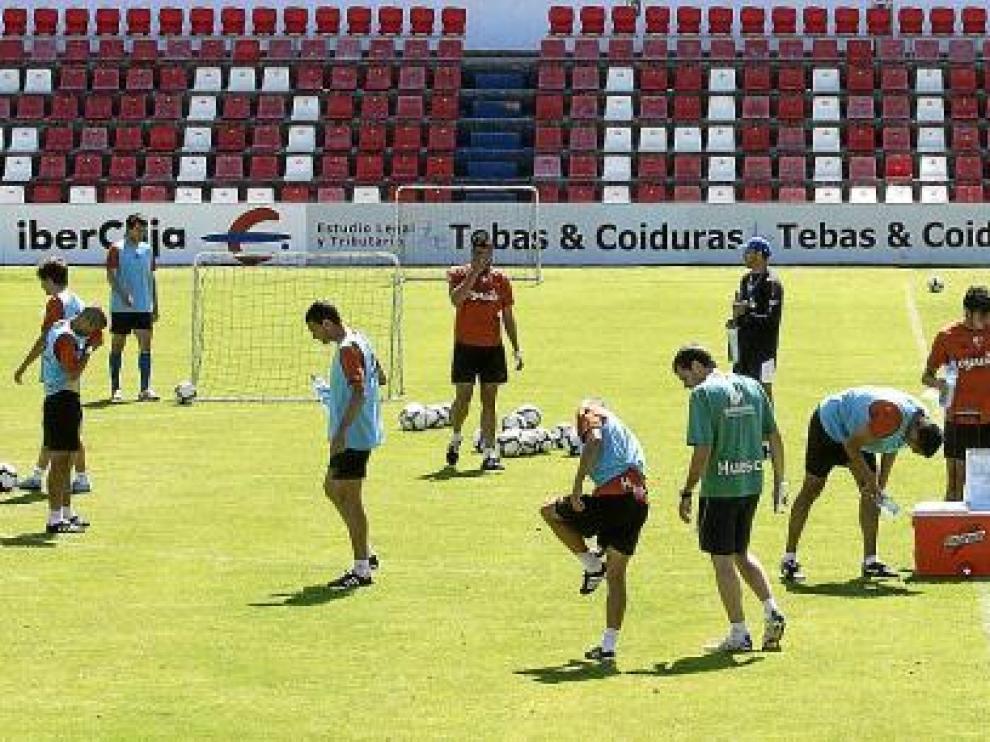 Los jugadores del Huesca, durante un interludio del entrenamiento de ayer durante el que se hidratan con agua.