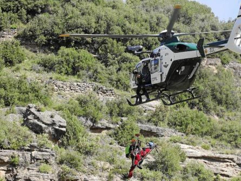 El helicóptero traslada con la grúa a un herido (de rojo) que va acompañado de un agente.