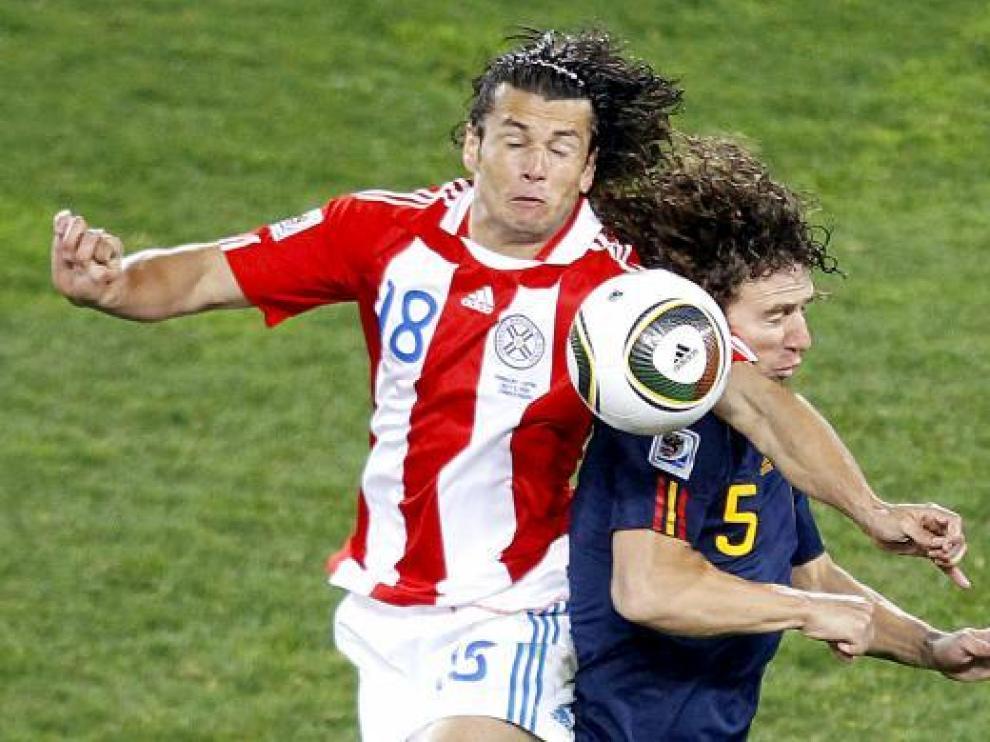 Puyol salta con el jugador paraguayo Nelson Valdez durante el partido de anoche.