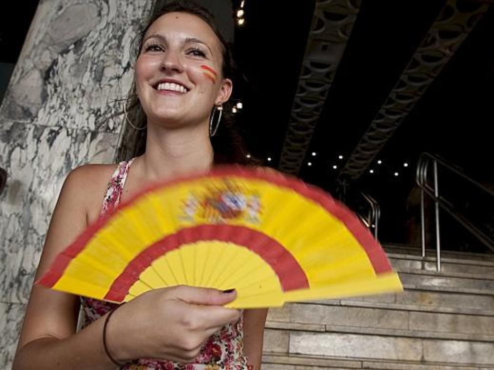 Una joven animadora de la selección española se abanica a la entrada de los cines Palafox.