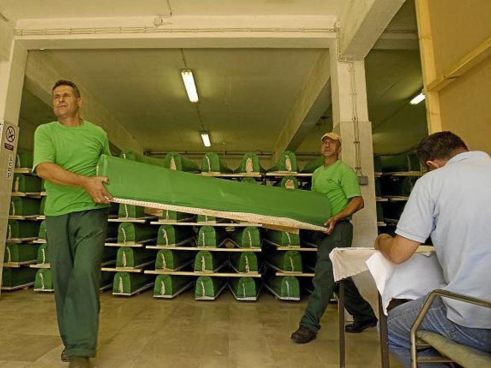Dos trabajadores cargan un ataúd en Visoko.