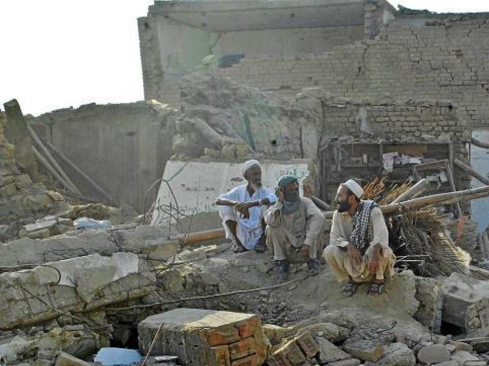 Tres hombres paquistaníes descansan entre las ruinas cercanas al lugar del atentado.