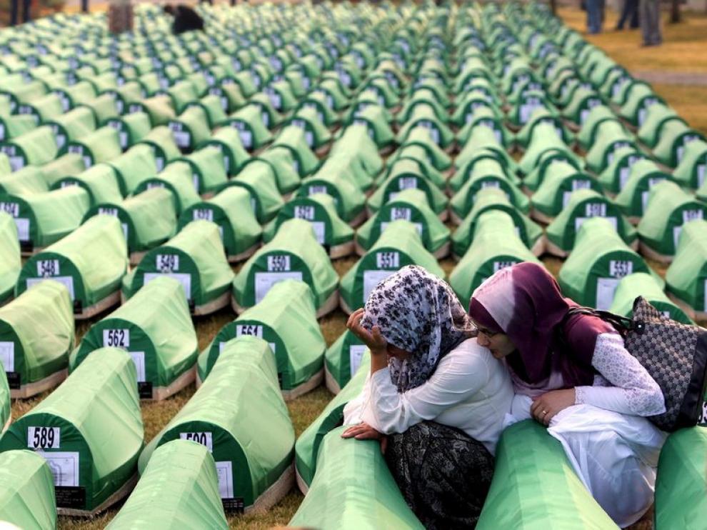 Dos mujeres se lamentan junto a los féretros de la matanza de Srebrenica