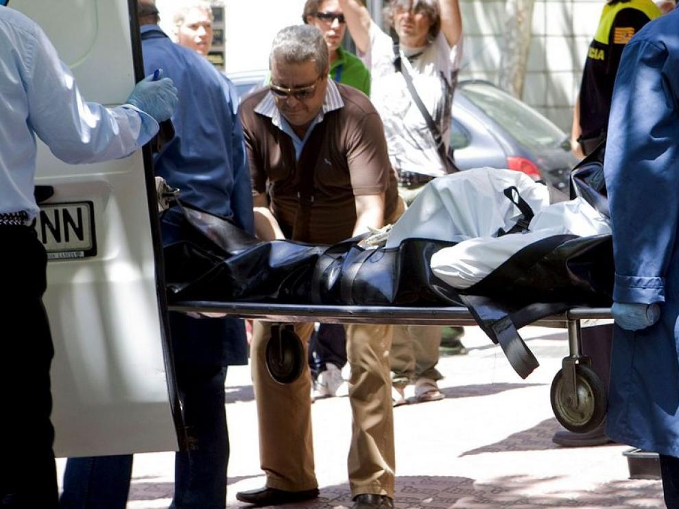 Miembros de la Hermandad de la Sangre de Cristo introducen en su furgón el cadáver de la mujer de nacionalidad ecuatoriana