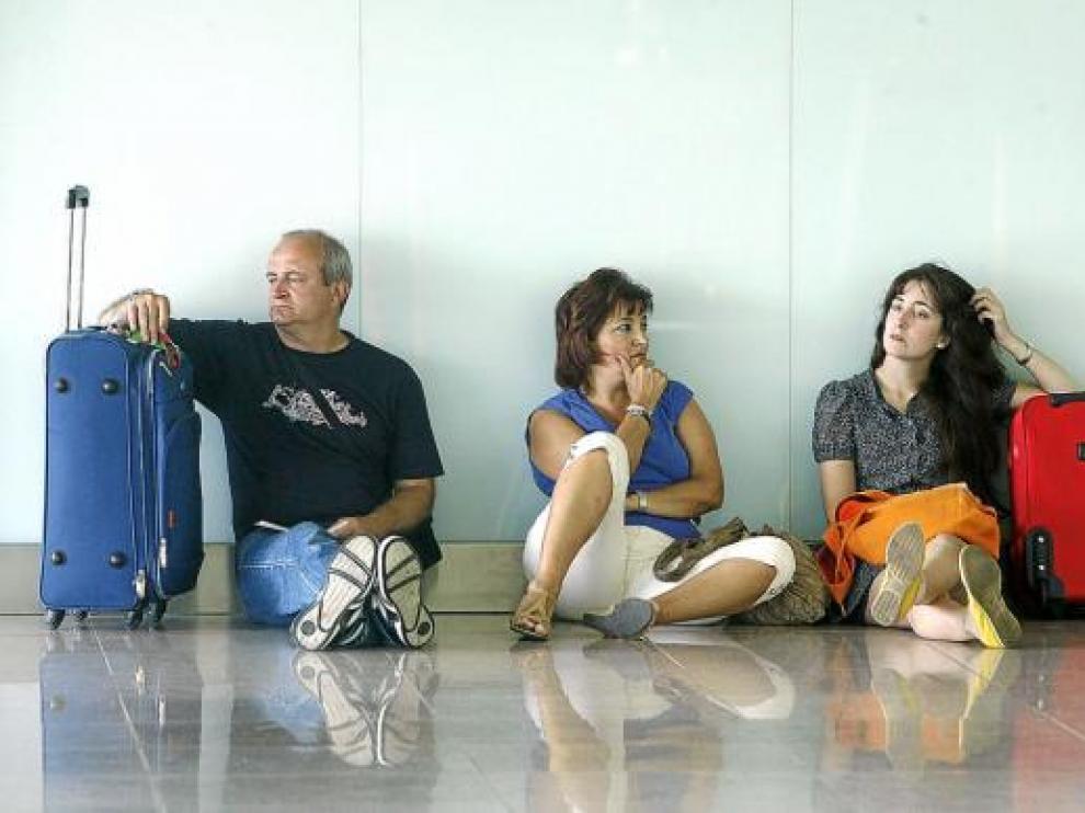 Varios pasajeros esperaban  ayer en el aeropuerto del Prat, donde se repitieron los retrasos.