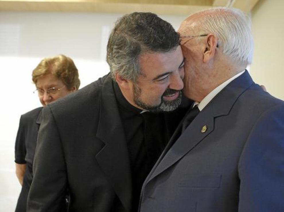 Carlos Escribano besa a su padre tras el anuncio de su nombramiento. Al fondo, su madre.