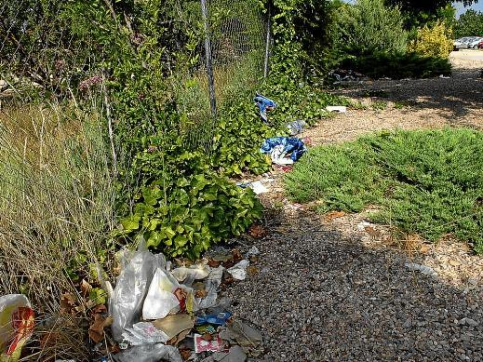 La basura se concentra al lado de la valla de la piscina de los Planos.