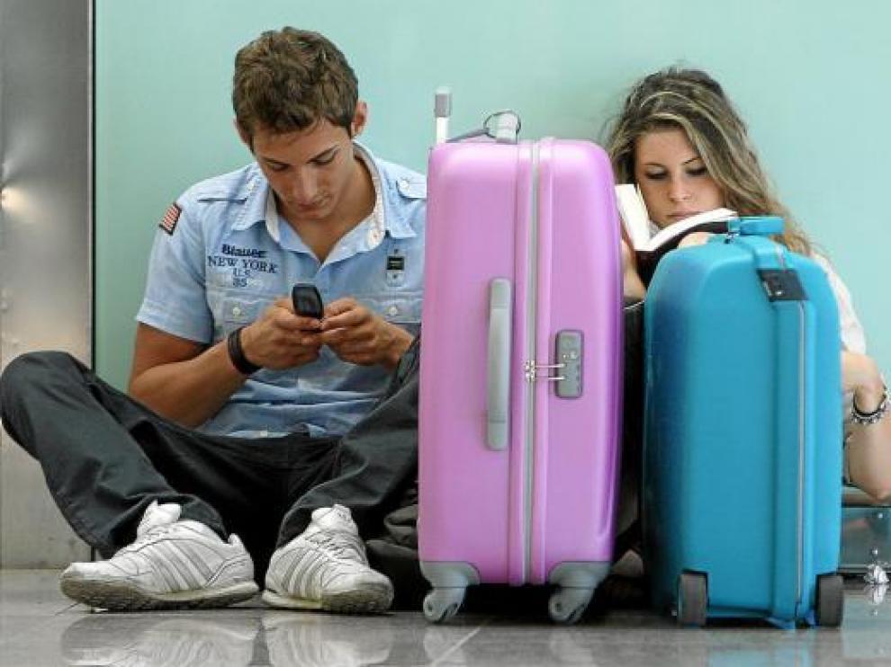 Dos jóvenes, de espera ayer en el aeropuerto del Prat, afectado por la huelga francesa de controladores.