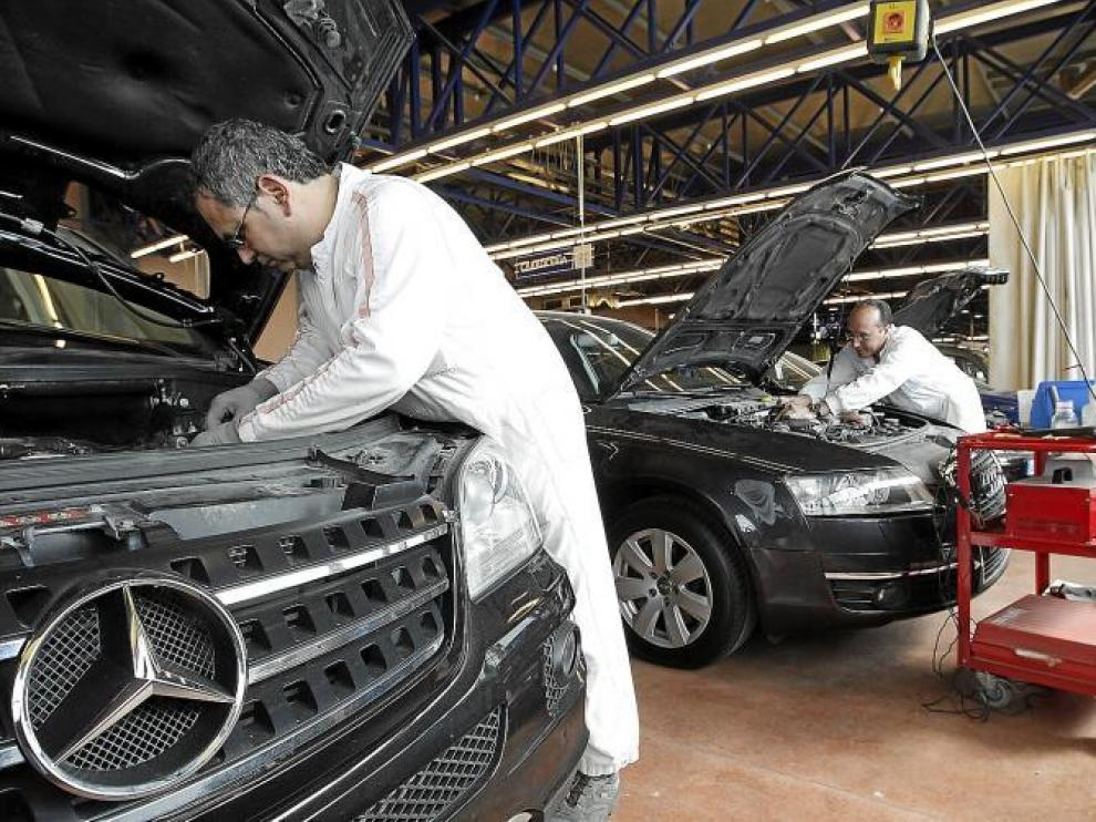 Dos trabajadores de Centro Zaragoza trabajan para identificar dos coches de alta gama recuperados estos días.