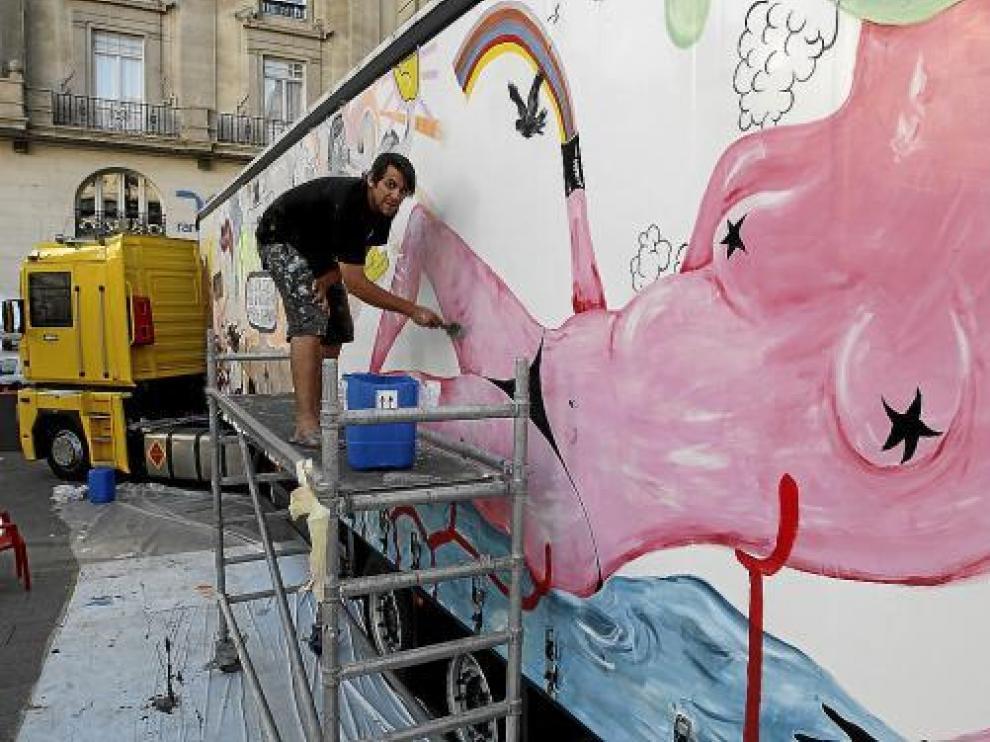 El artista Leto da las últimas pinceladas a su pintura mural en el lateral del remolque.