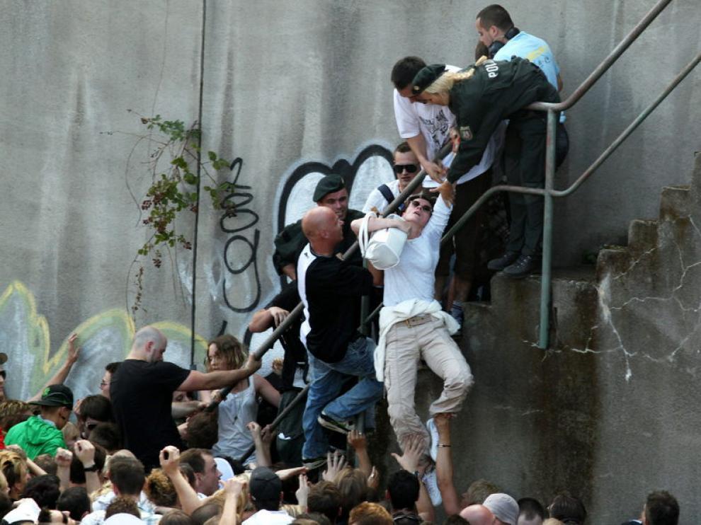 """La policía ayuda a una mujer durante los momentos de pánico vividos en la """"Love Parade""""."""
