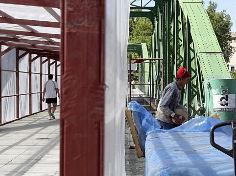 Los trabajos en los arcos que aún quedan por pintar y el pasadizo habilitado en el puente.