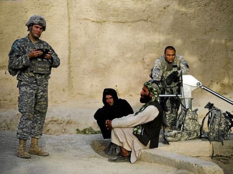 Dos soldados estadounidenses charlan con dos civiles afganos de la provincia de Kandahar.