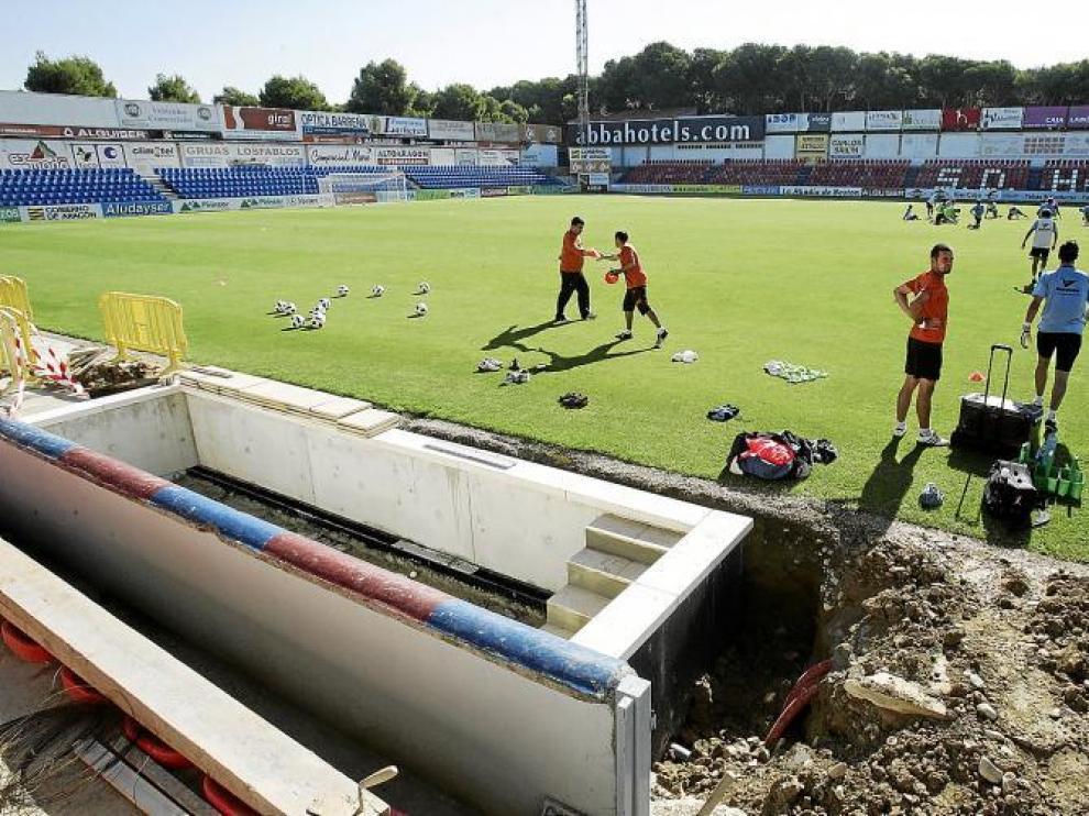 Los jugadores del Huesca, durante el entrenamiento de ayer en El Alcoraz. En primer término, las obras en los banquillos.