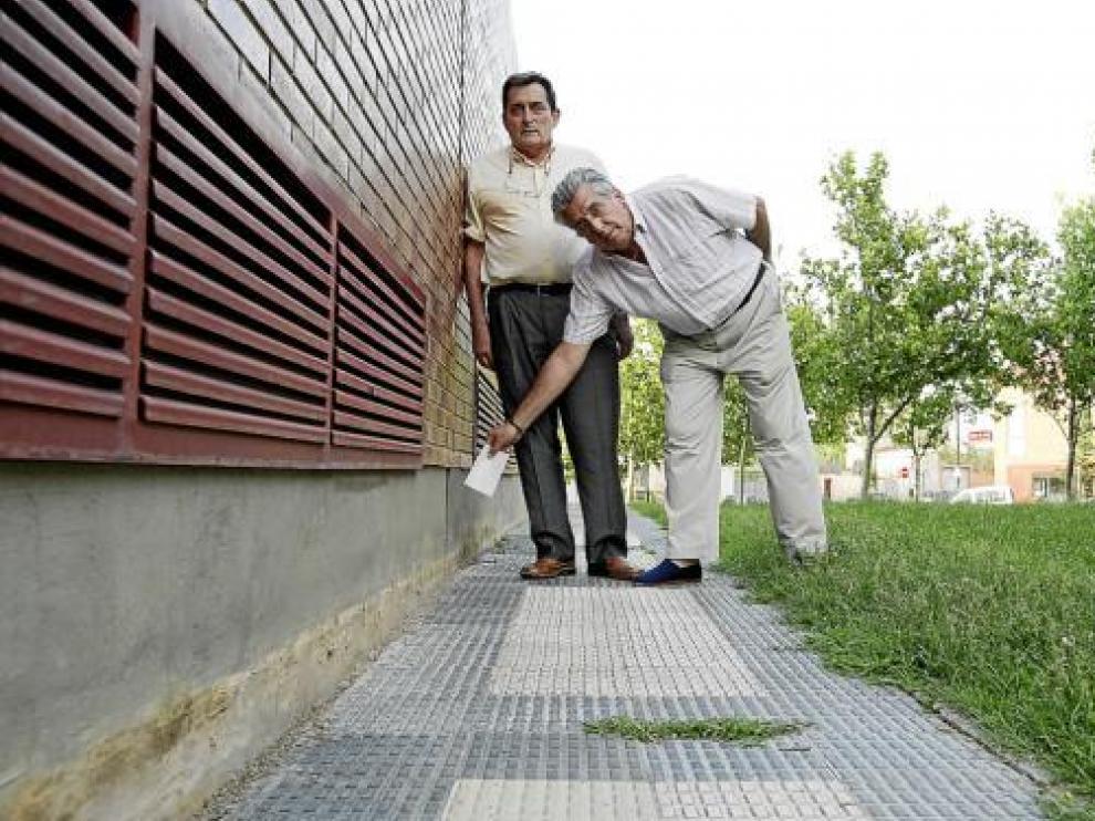Francisco (a la derecha) y Antonio, junto a la marca que señala el nivel al que estaba la acera.
