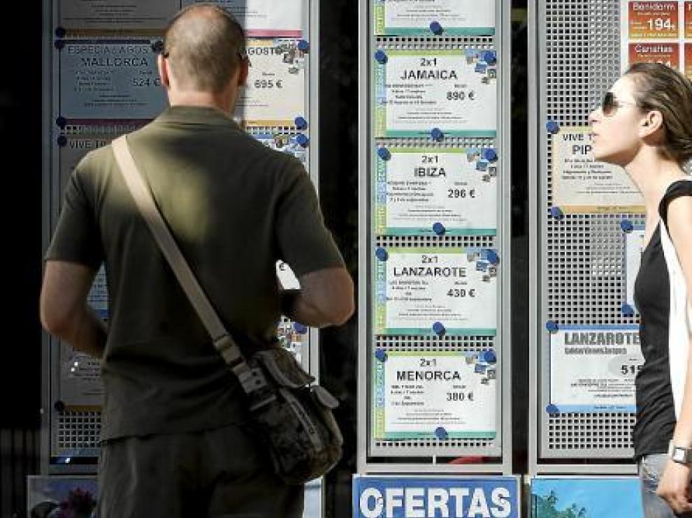 Dos jóvenes ojeaban ayer las ofertas de una agencia de viajes de Zaragoza.