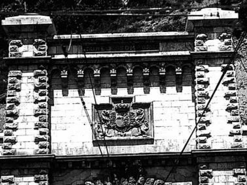 Escudo original de 1928 con corona monárquica. El túnel fue inaugurado el 18 de julio por Alfonso XIII y el presidente de la República Francesa, Gaston Doumerguen. Hasta la dictadura, en la boca española del paso subterráneo lucía esta obra de cantería.