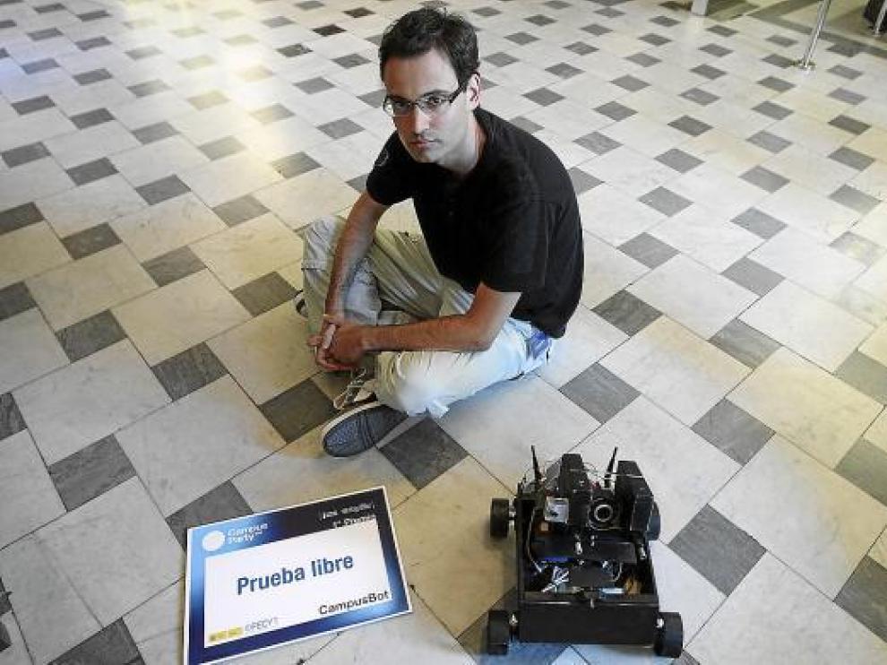 David Meléndez, sentado en el suelo con su robot y el diploma que ganó en Valencia.