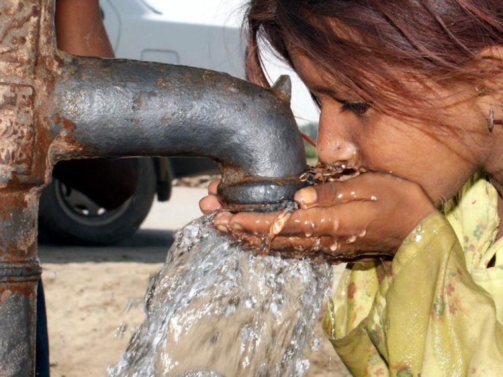 Una niña bebe agua en un campo de acogida a los afectados por las inundaciones