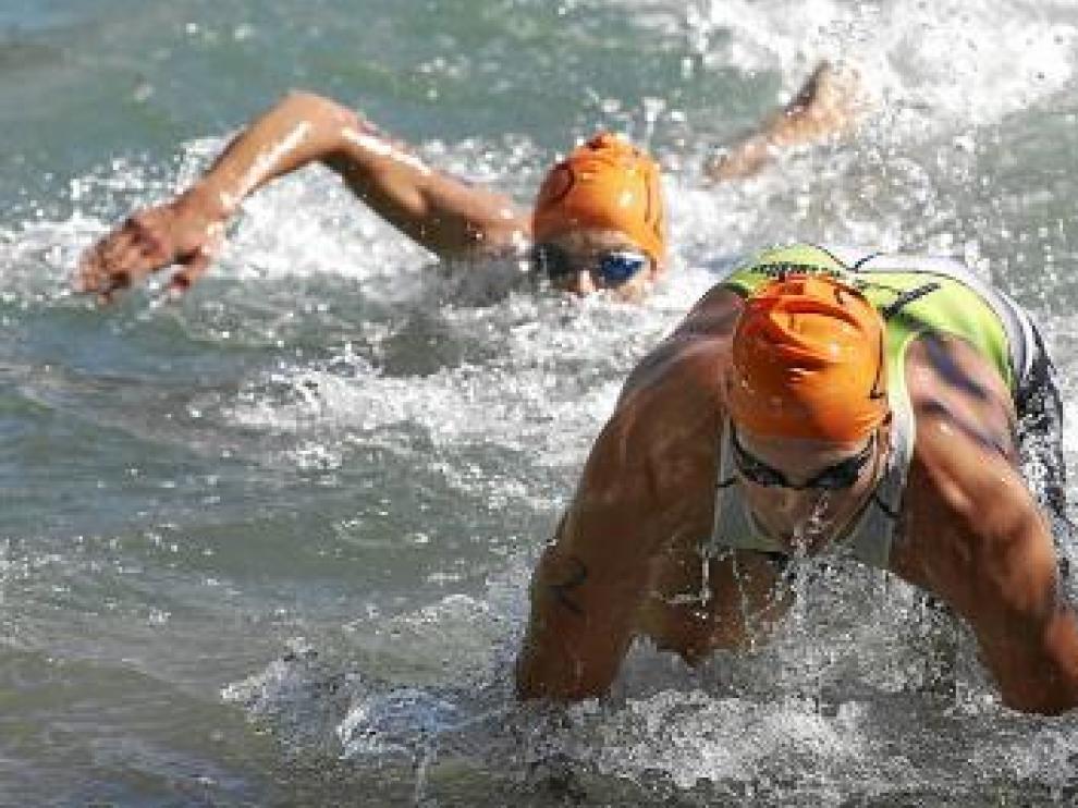 Dos participantes nadan en la primera prueba del triatlón.