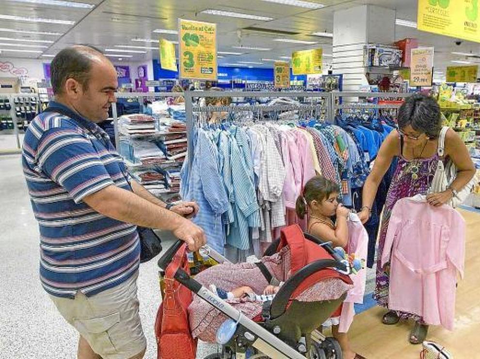 Una familia ultimaba ayer las compras de ropa y material escolar en un centro comercial.