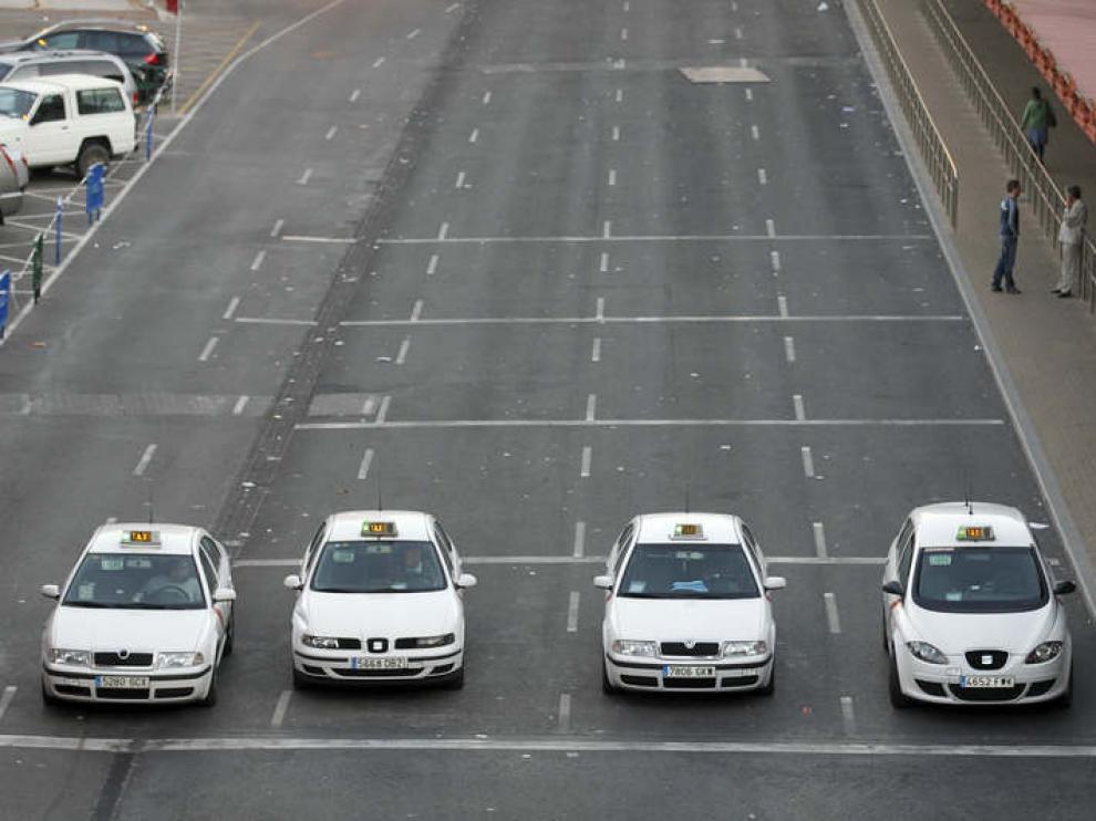 Cuatro taxis parados en la entrada de la estación de Atocha de Madrid, esperando clientes.