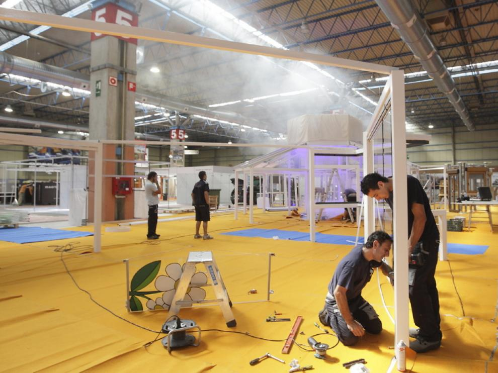 Unos obreros ultiman los preparativos en el interior de la Feria de Muestras