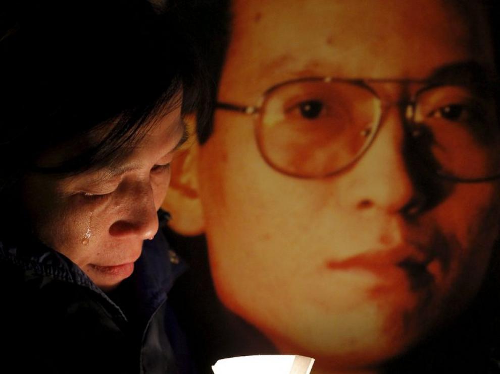 Una activista llorando junto a una foto del disidente chino Liu Xiaobo.