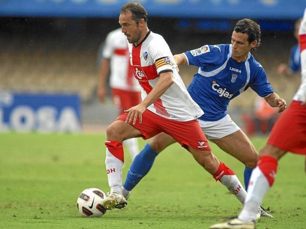 Luis Helguera conduce el balón y salva la entrada de un futbolista del Xerez durante el partido de ayer en Chapín.