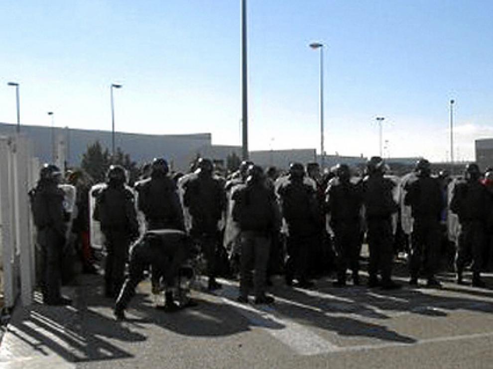 Agentes de la Guardia Civil, frente a los trabajadores concentrados ayer en la nave de Pedrola donde se guardaban asientos de Lear.