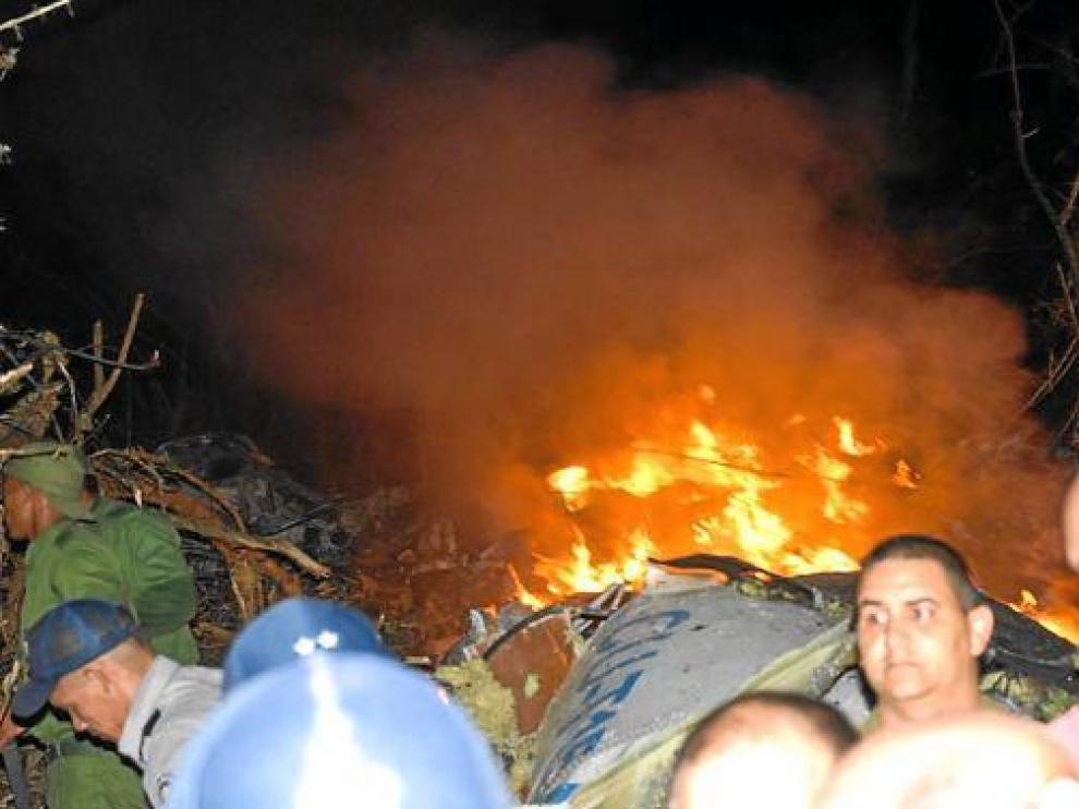Varias personas tratan de buscar supervivientes en el avión, en llamas, que se estrelló en Cuba.