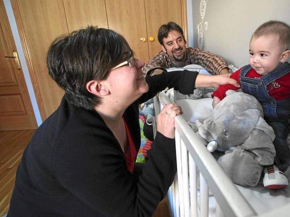 Juan, el bebé de cinco meses risueño y simpático, posa en su dormitorio junto a sus padres y con su peluche favorito.