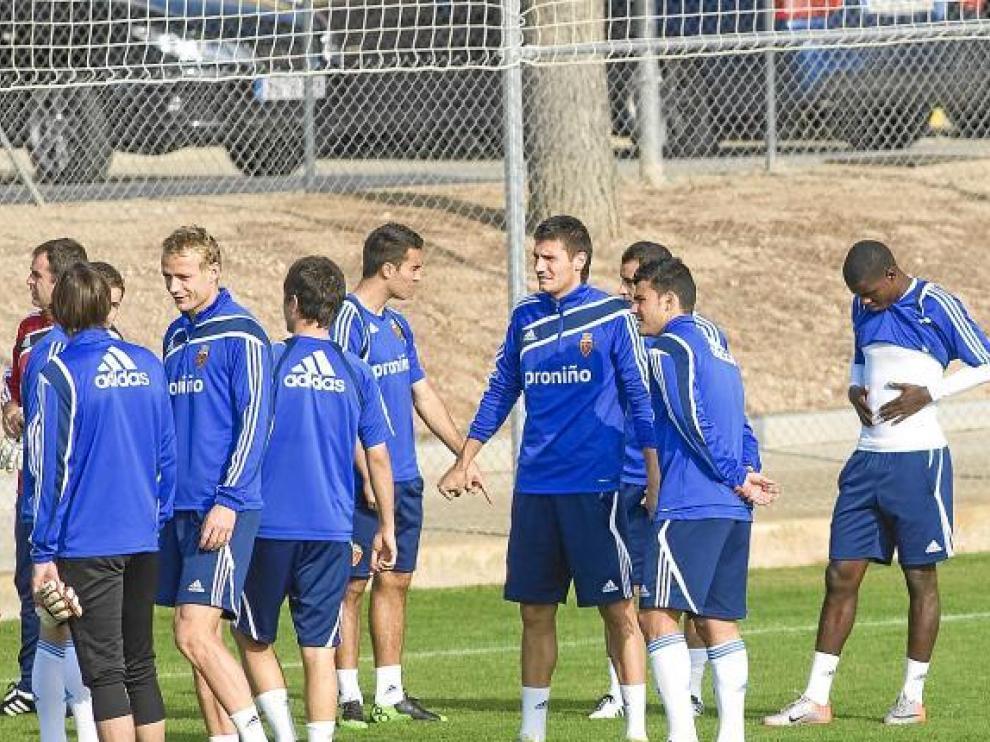 La plantilla del Real Zaragoza dialoga durante el entrenamiento del viernes.