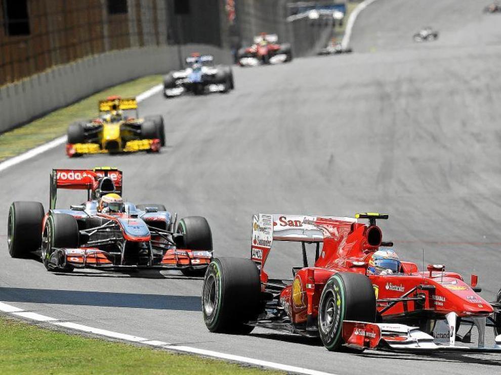El piloto español Fernando Alonso (Ferrari), supera a su rival Lewis Hamilton (McLaren) durante el Gran Premio de Brasil.