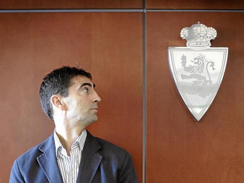José Aurelio Gay, al lado del escudo del Real Zaragoza en la sede del club.