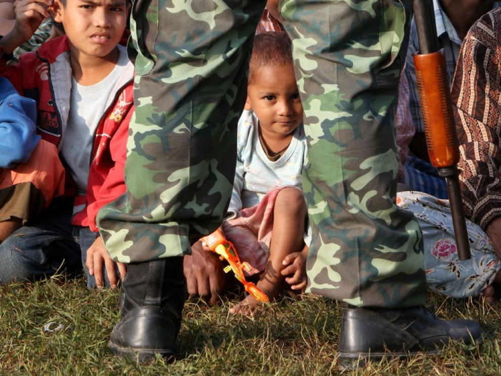 Un soldado tailandés vigila a refugiados birmanos que permanecen en la base de la policía fronteriza en Mae Sot (Tailandia)