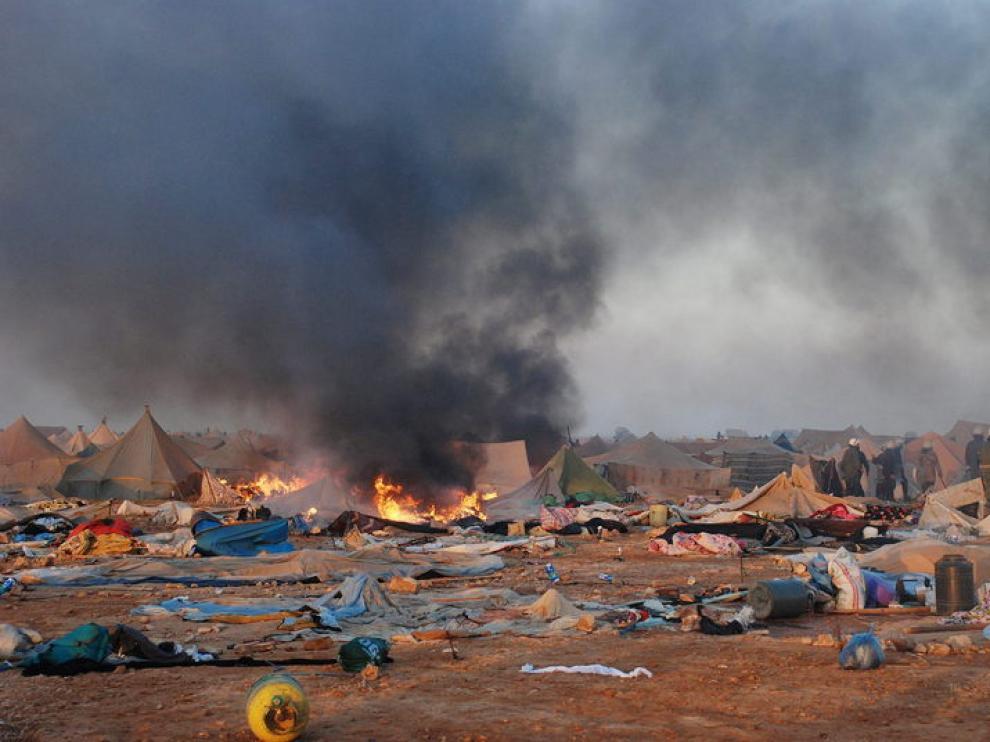 En el campamento desalojado arden en llamas algunas de las jaimas destruídas