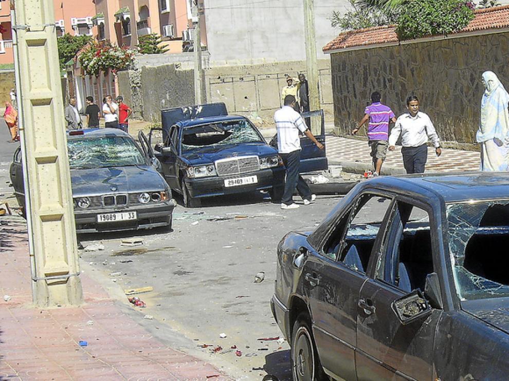 Varios saharauis observan tres coches con los cristales rotos, ayer en una calle de El Aaiún