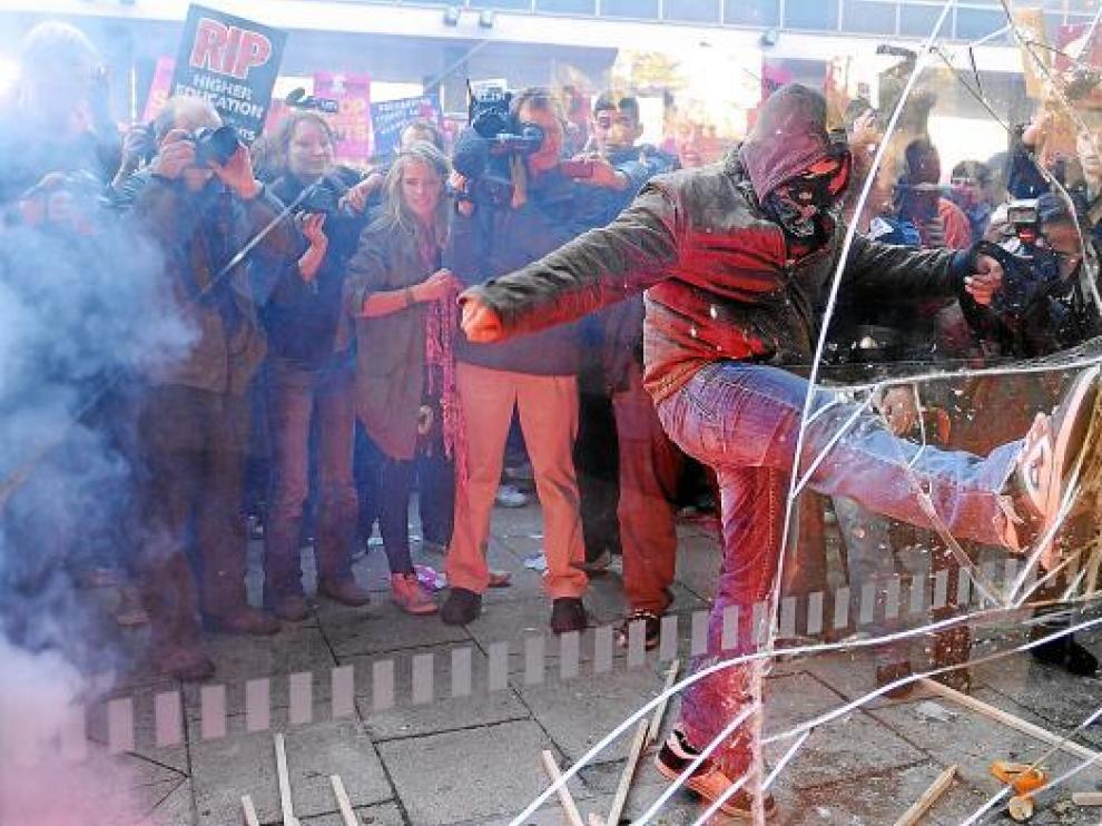 Uno de los manifestantes golpea con la pierna el cristal de la sede del partido.