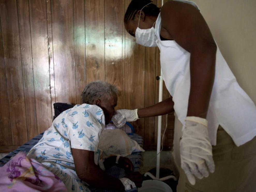 Una mujer da de beber a una paciente de cólera en Haití
