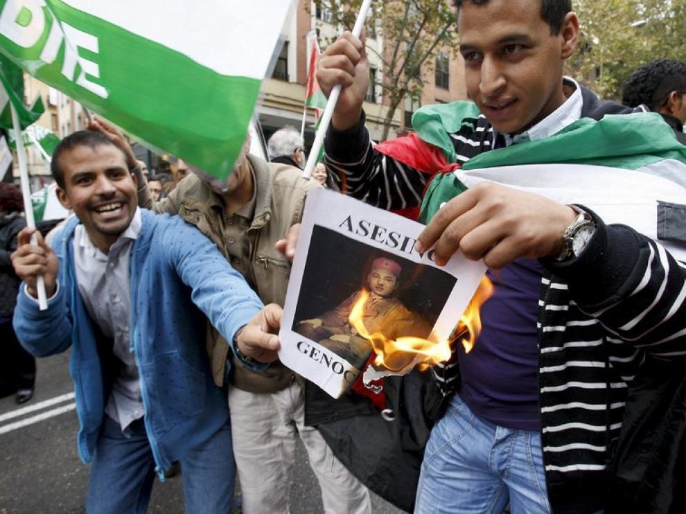 Dos ciudadanos marroquíes queman una fotografía del rey de Marruecos, Mohamed VI, durante la manifestación organizada en Madrid