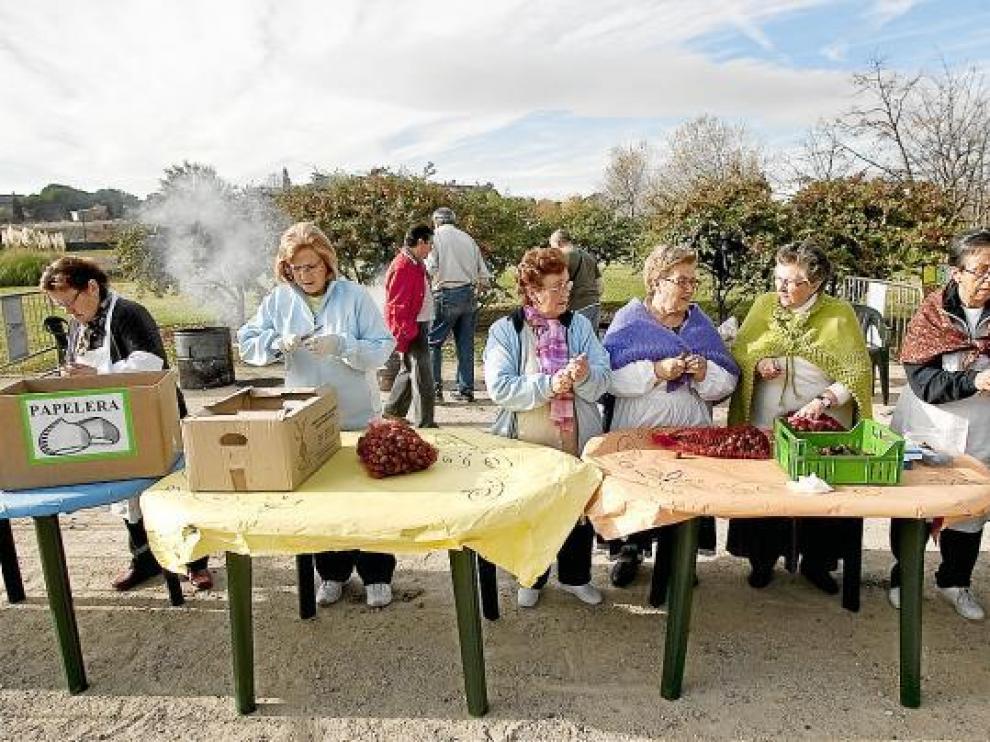 Unas mujeres preparan las castañas que se repartieron ayer gratis en el parque Oliver.