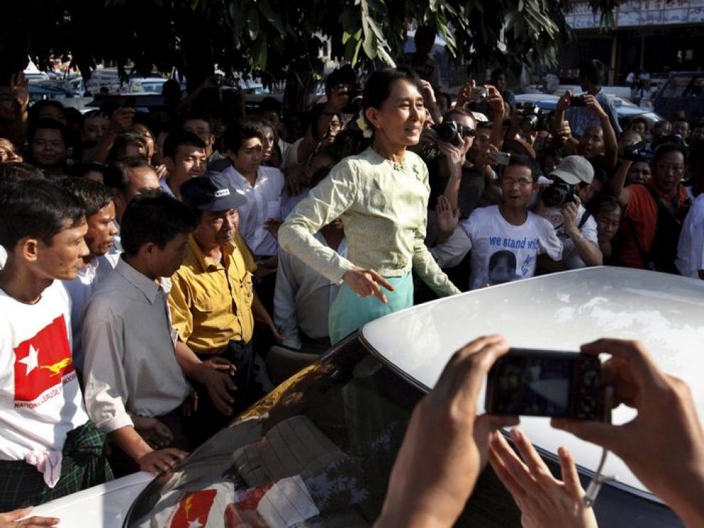 Aung San Suu Kyi saluda a sus seguidores a la salida de la sede de su partido, después de terminar su primer día de trabajo