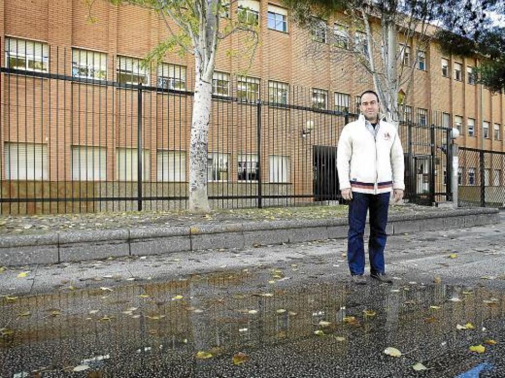 Francisco Sanz, vicepresidente de la Asociación de Padres, junto al charco en la puerta del colegio.