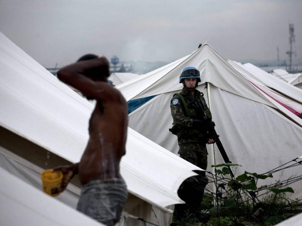 Un hombre se lava ante la atenta mirada de un soldado, ayer, en el campamento de Cite Soleil, Puerto Príncipe