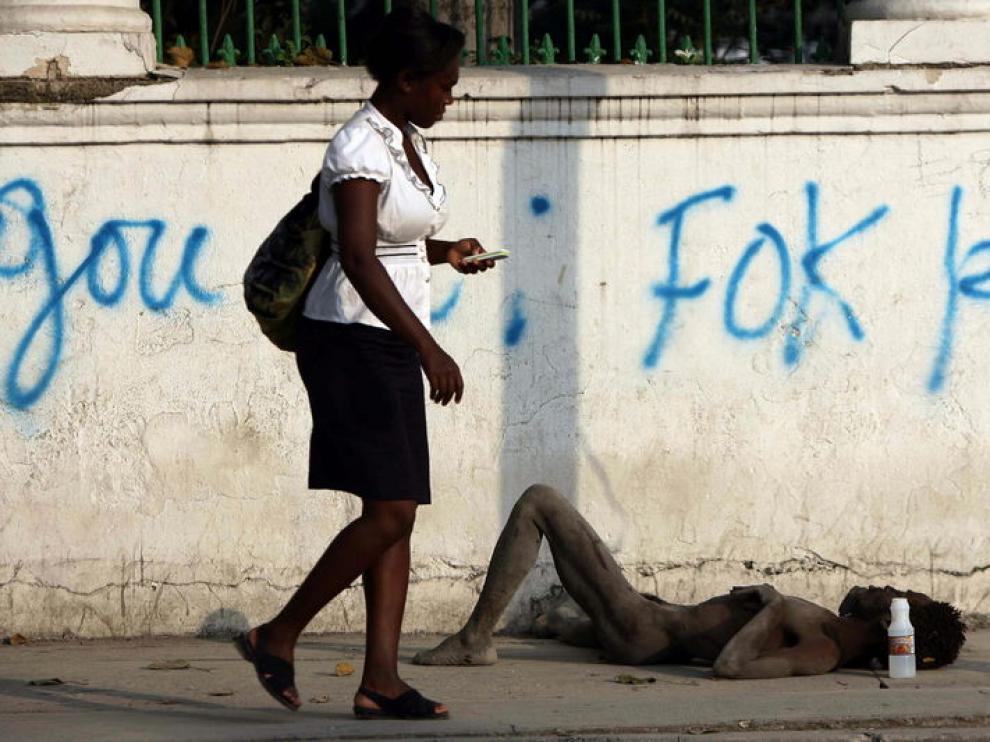 Una mujer pasa, atenta a su móvil, junto a un cadáver tirado en la acera