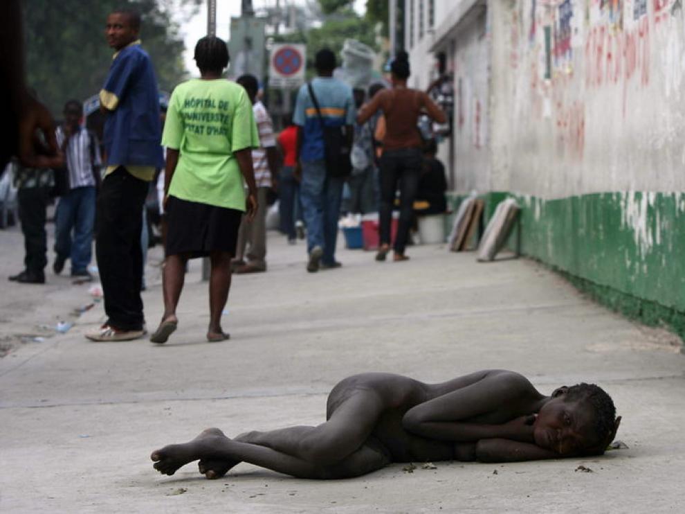 Una mujer enferma de cólera tumbada cerca del Hospital General, en Haití